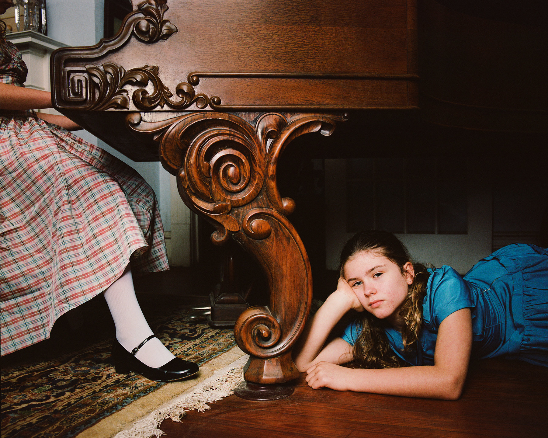A young girl lies under a piano, and another girl is pictured from the waist down seated at the piano