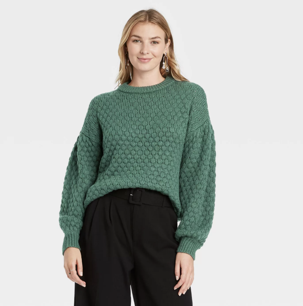 a model in a green sweater with a circle pattern on it and balloon sleeves