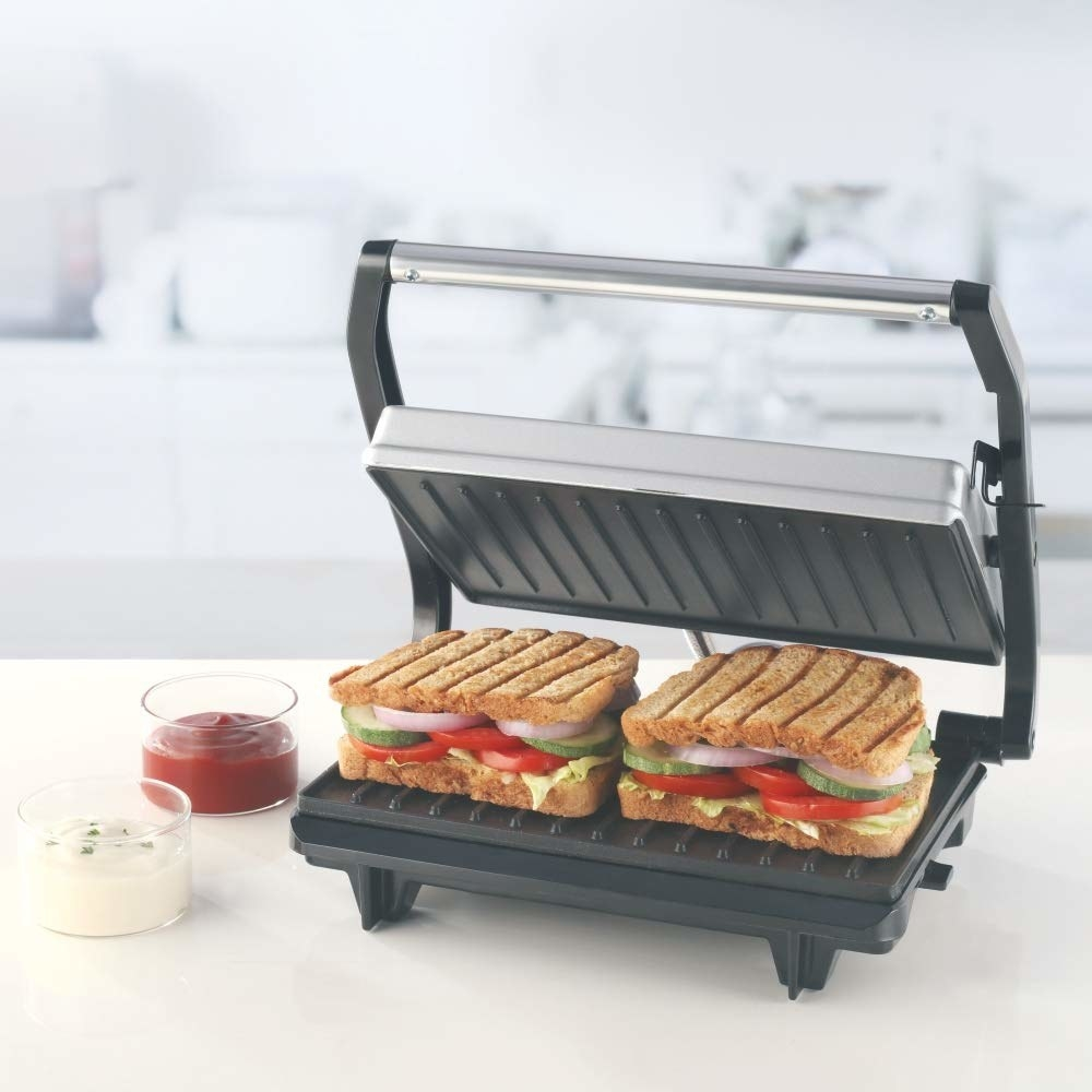 Sandwich maker on a kitchen countertop with 2 grilled sandwiches on it