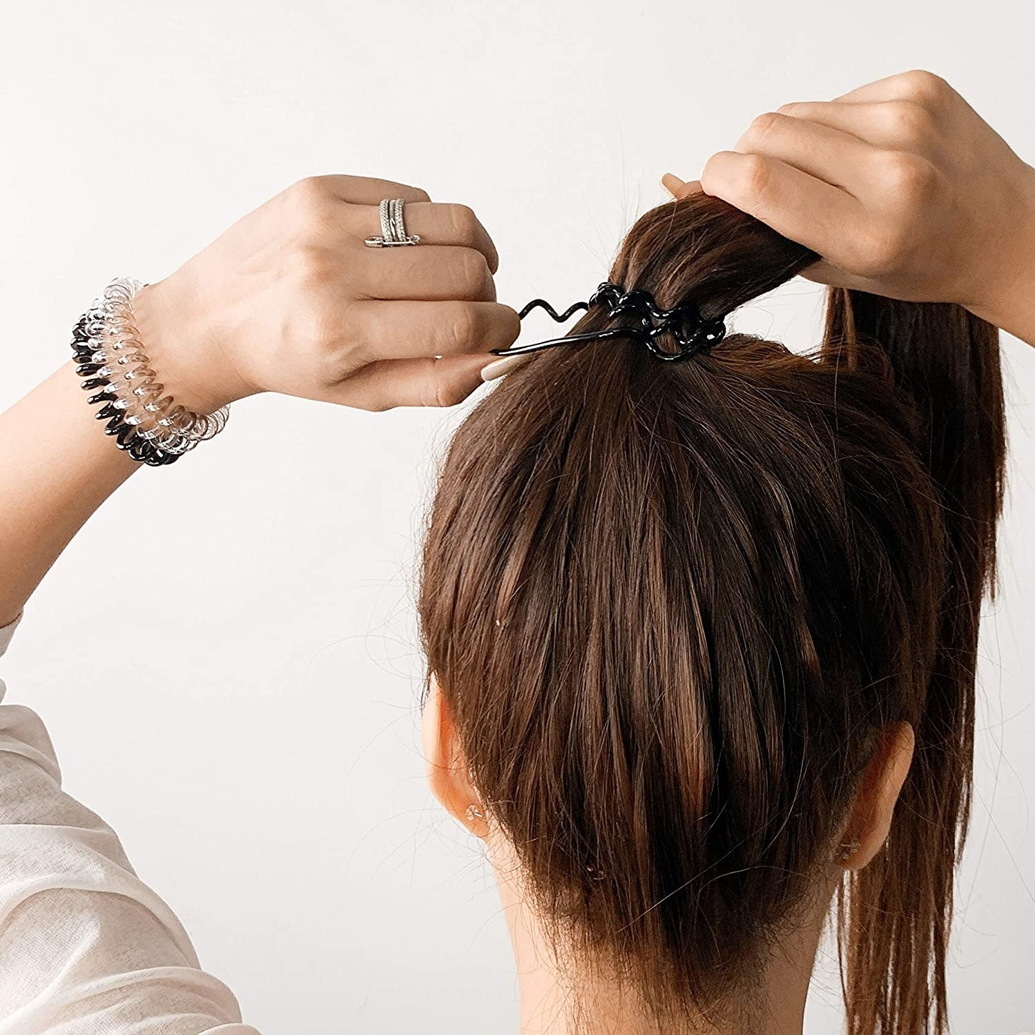 A woman tying a ponytail with coil hair tie
