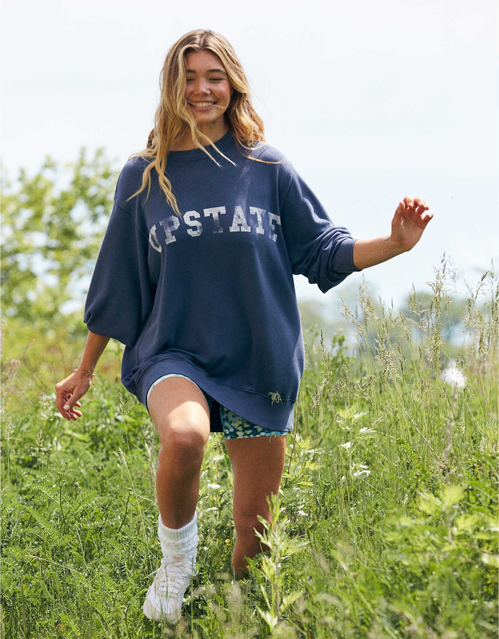 """a model walking in grass in an oversized blue sweatshirt that says """"upstate"""" on it"""