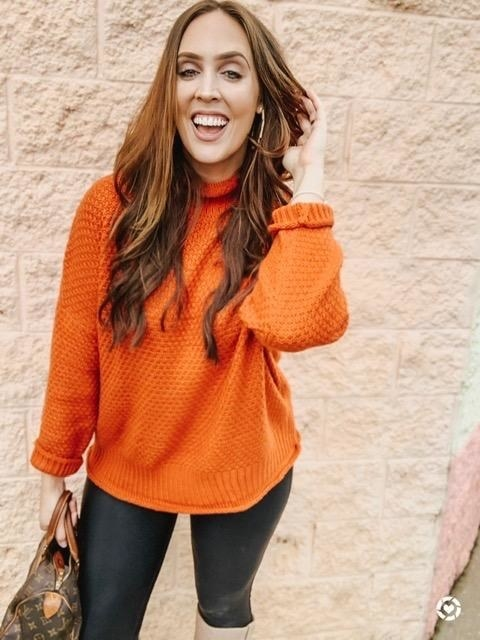 Reviewer photo of a person wearing an orange mock neck sweater with black leggings