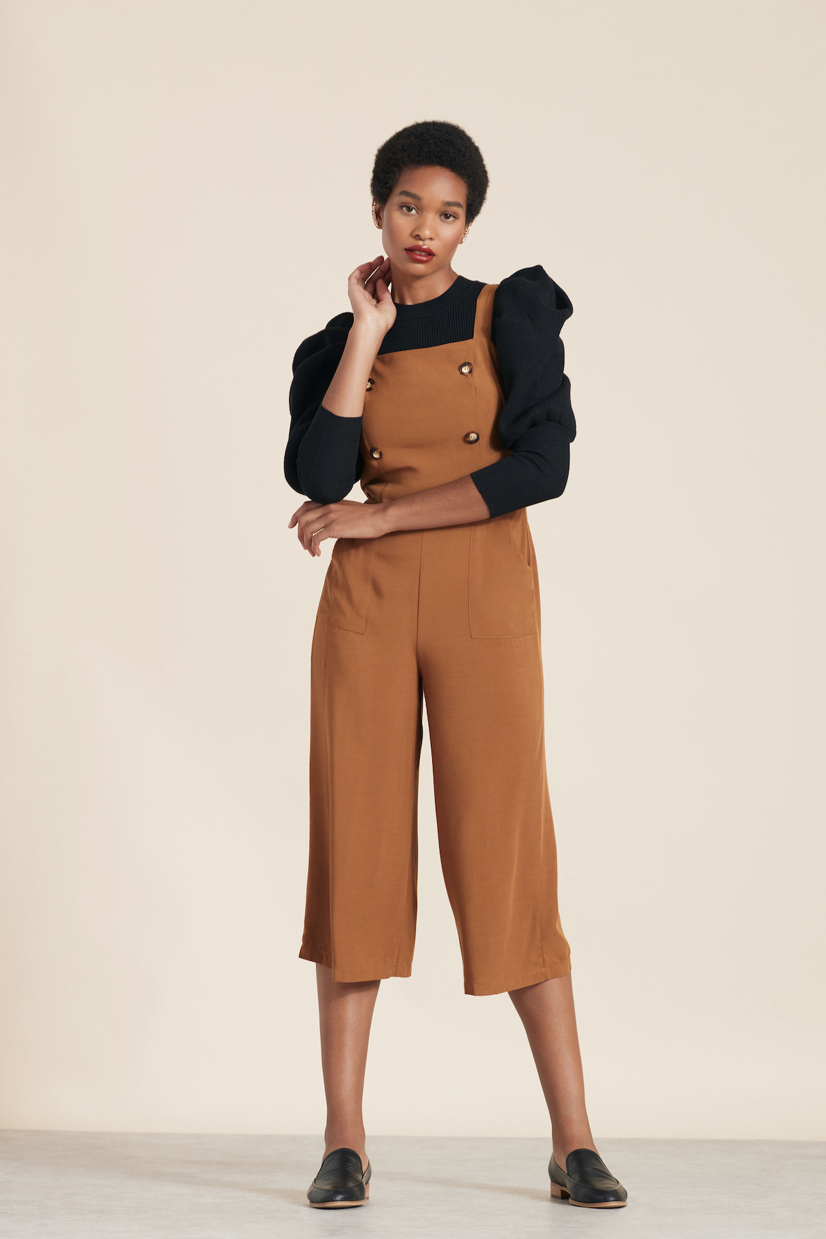 a model in a burnt orange jump suit with cropped wide legs and button bib detailing
