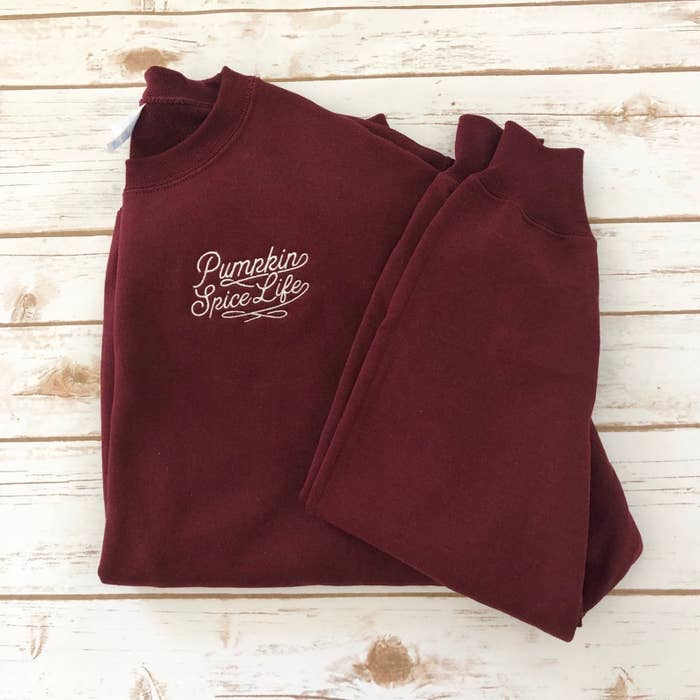 a maroon colored sweatshirt with white embroidery that says pumpkin spice life on it