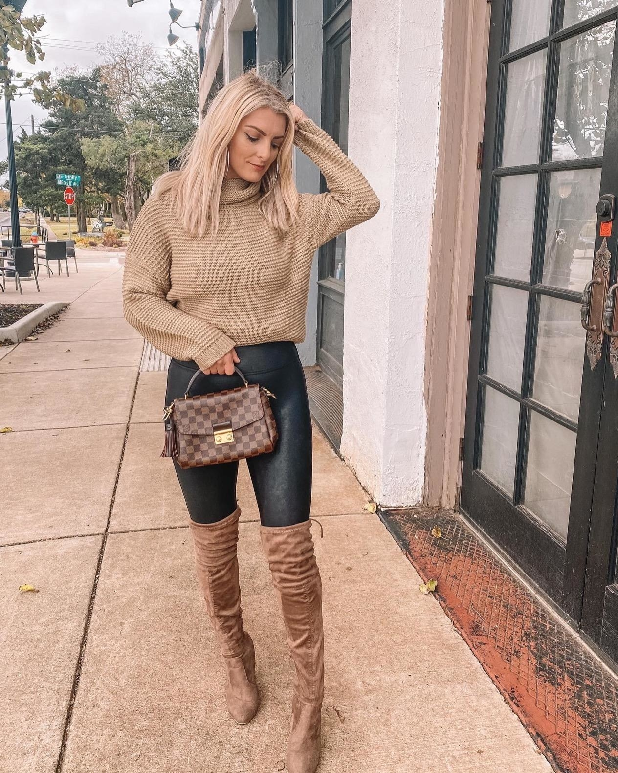 Reviewer photo of a person wearing a light brown sweater, dark jeans, and brown over the knee boots