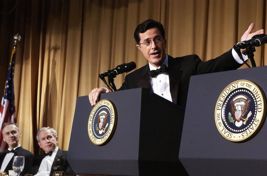 Stephen Colbert performs while Bush watches
