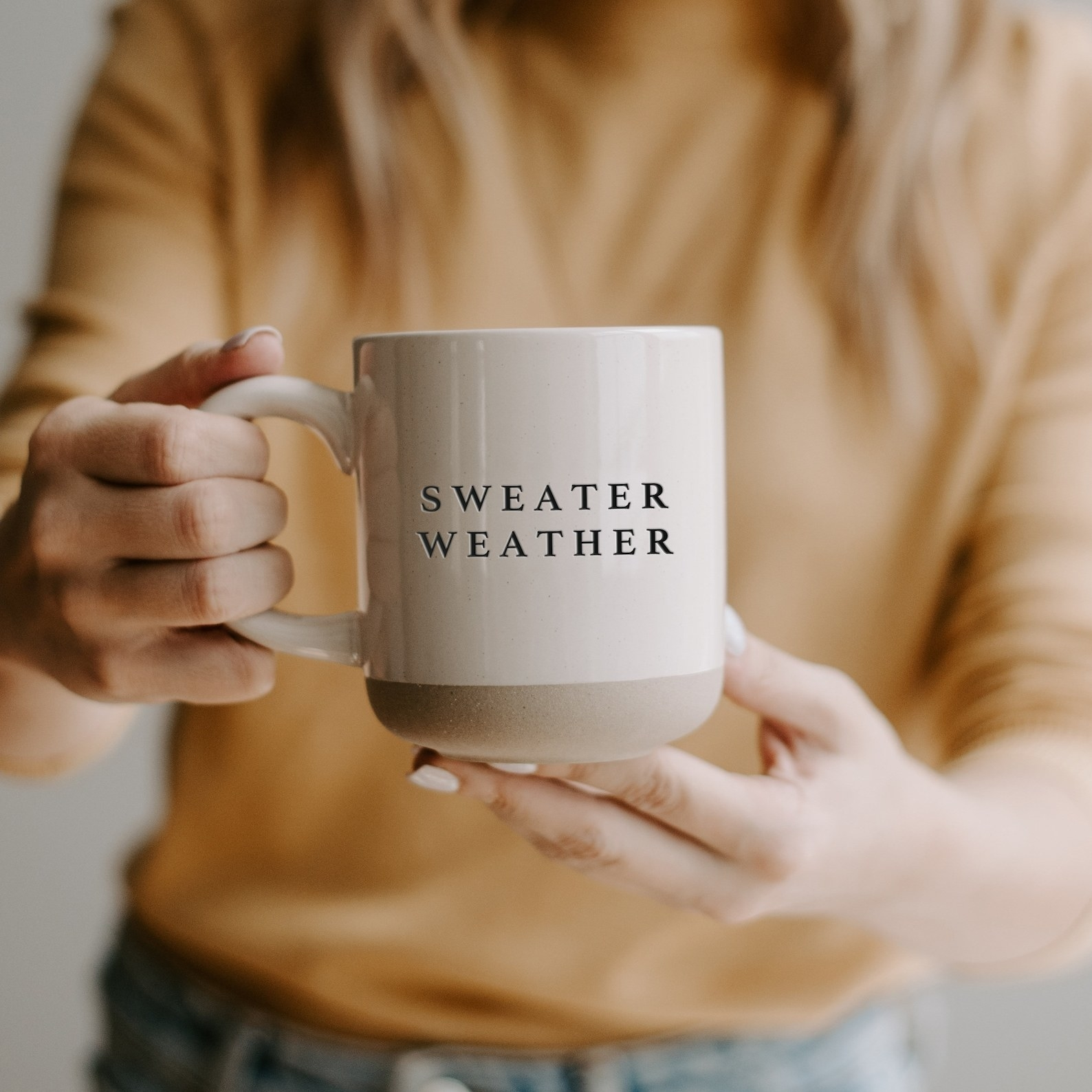 """a model holding a white mug with a grey stone bottom and """"sweater weather"""" etched in it in black"""