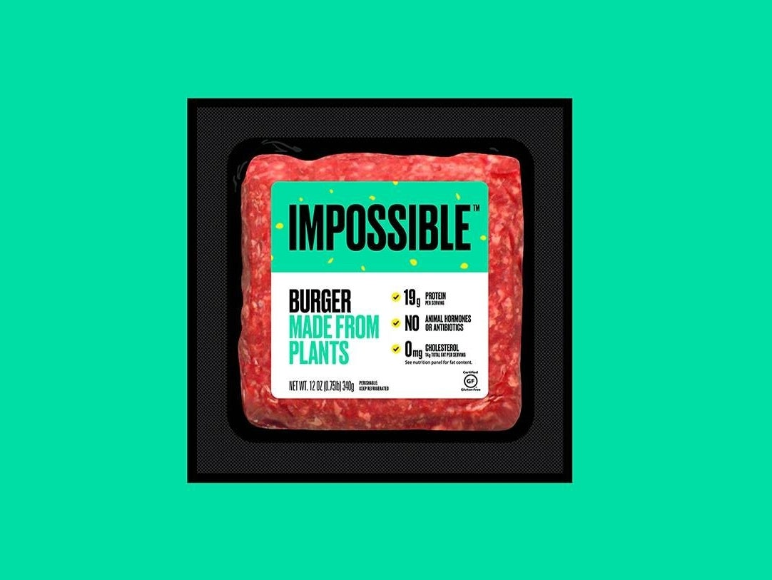 A package of impossible meat over a turquoise background