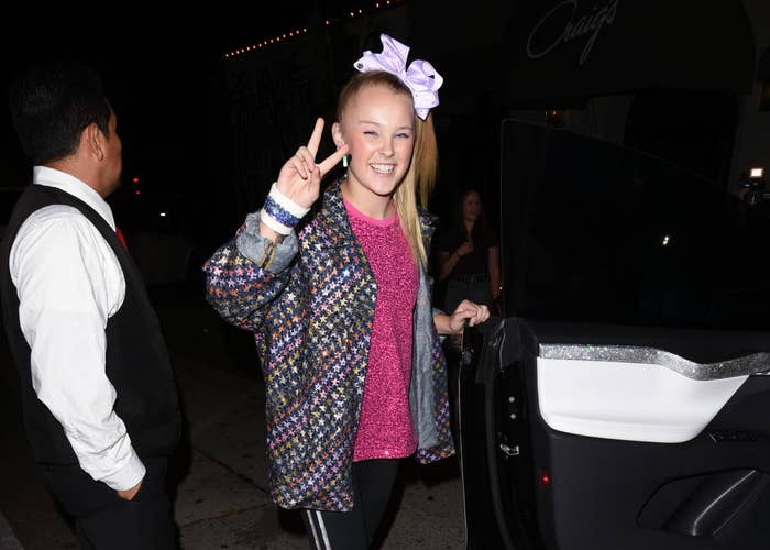 JoJo Siwa smiling giving the peace sign before entering a car