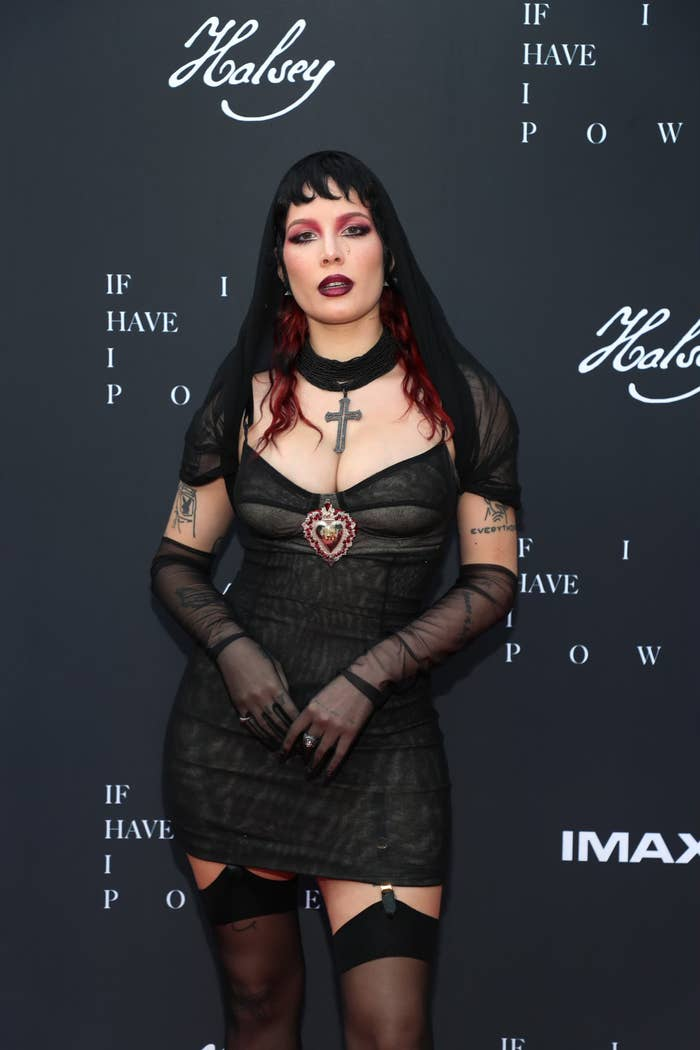 Halsey on the red carpet in a short dark dress, matching gloves, a veil and stockings