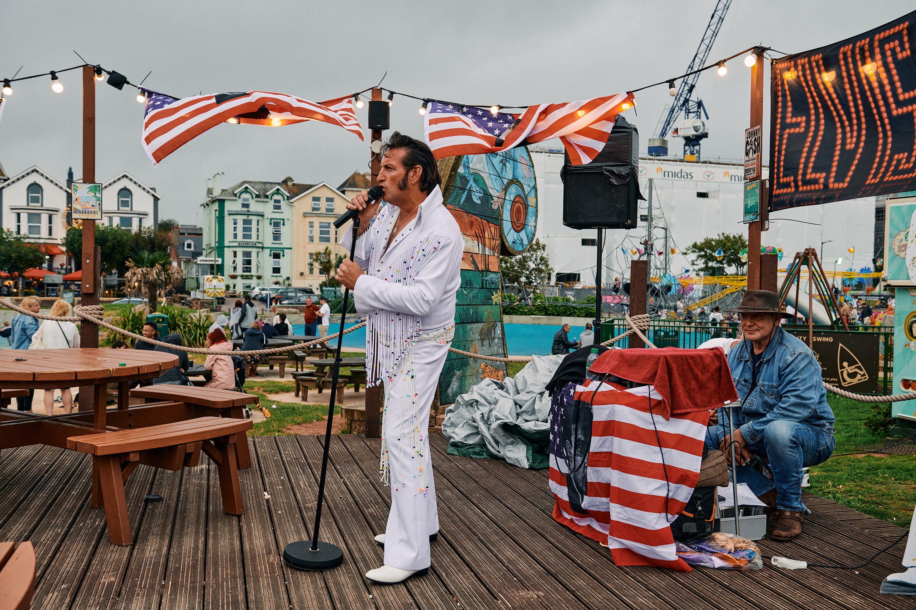 An Elvis impersonator sings on a wooden stage, with a man crouching behind the soundboard behind him