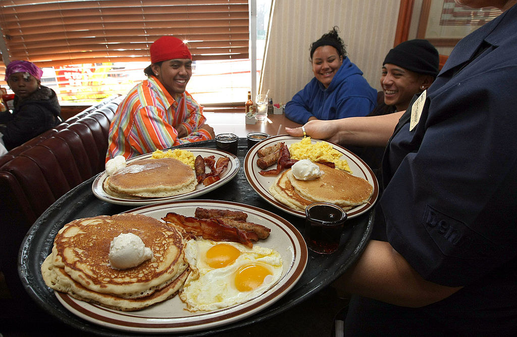 Three smiling people sitting at a table in a diner looking at plates of pancakes, sausage/bacon, and eggs that they're about to be served