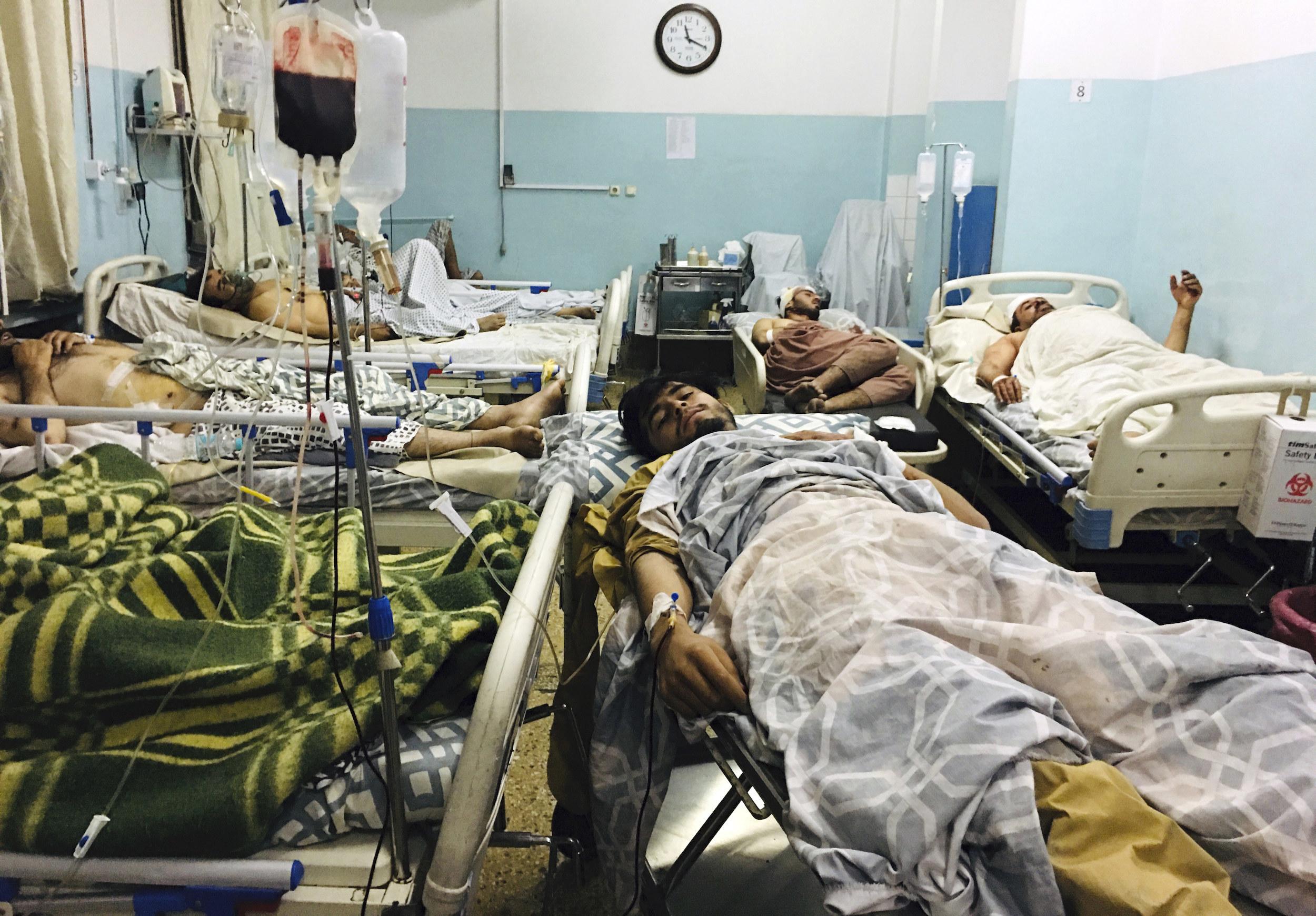 Five wounded men lie in hospital beds