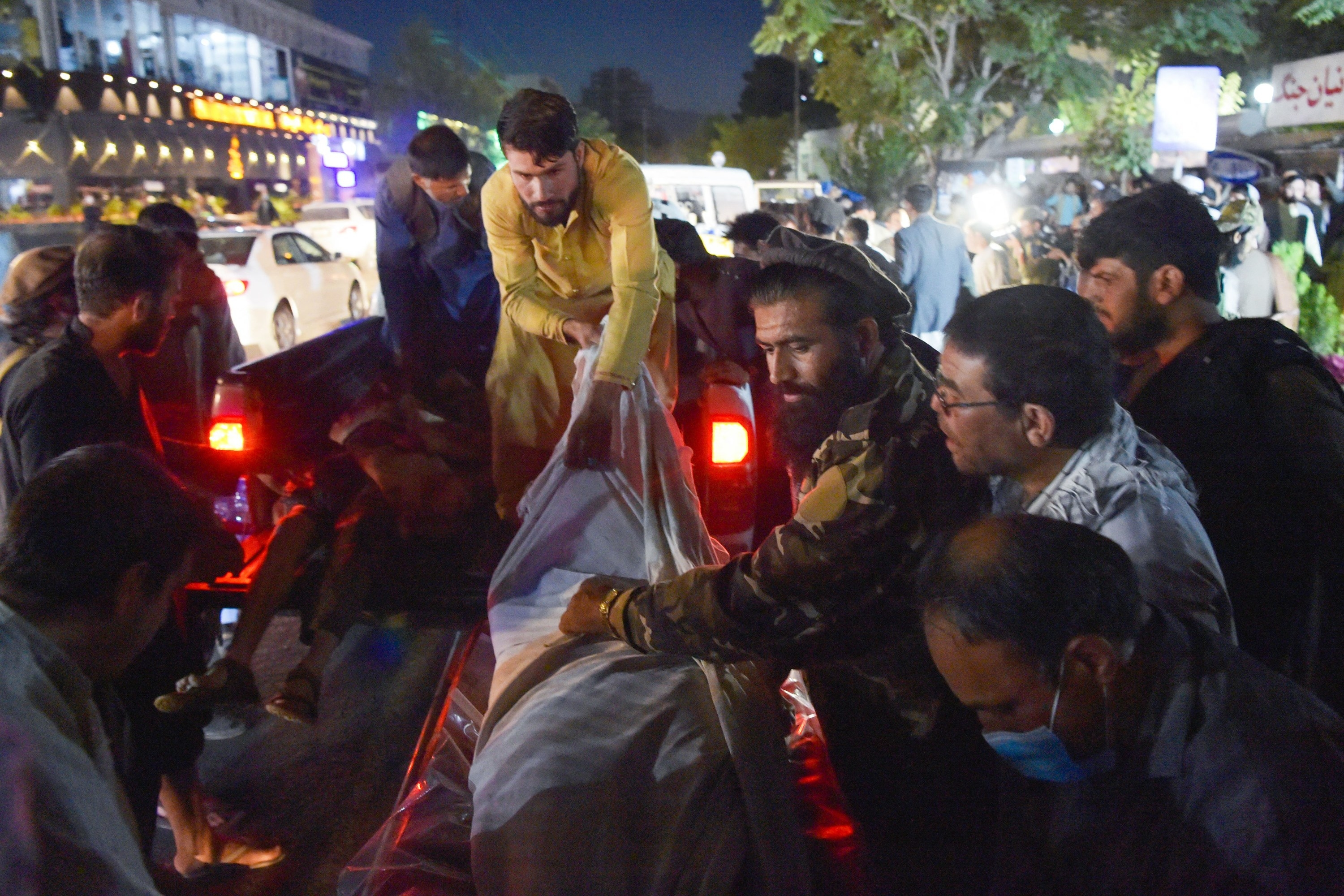 Afghan citizens gather and help transport a body wrapped in a blanket