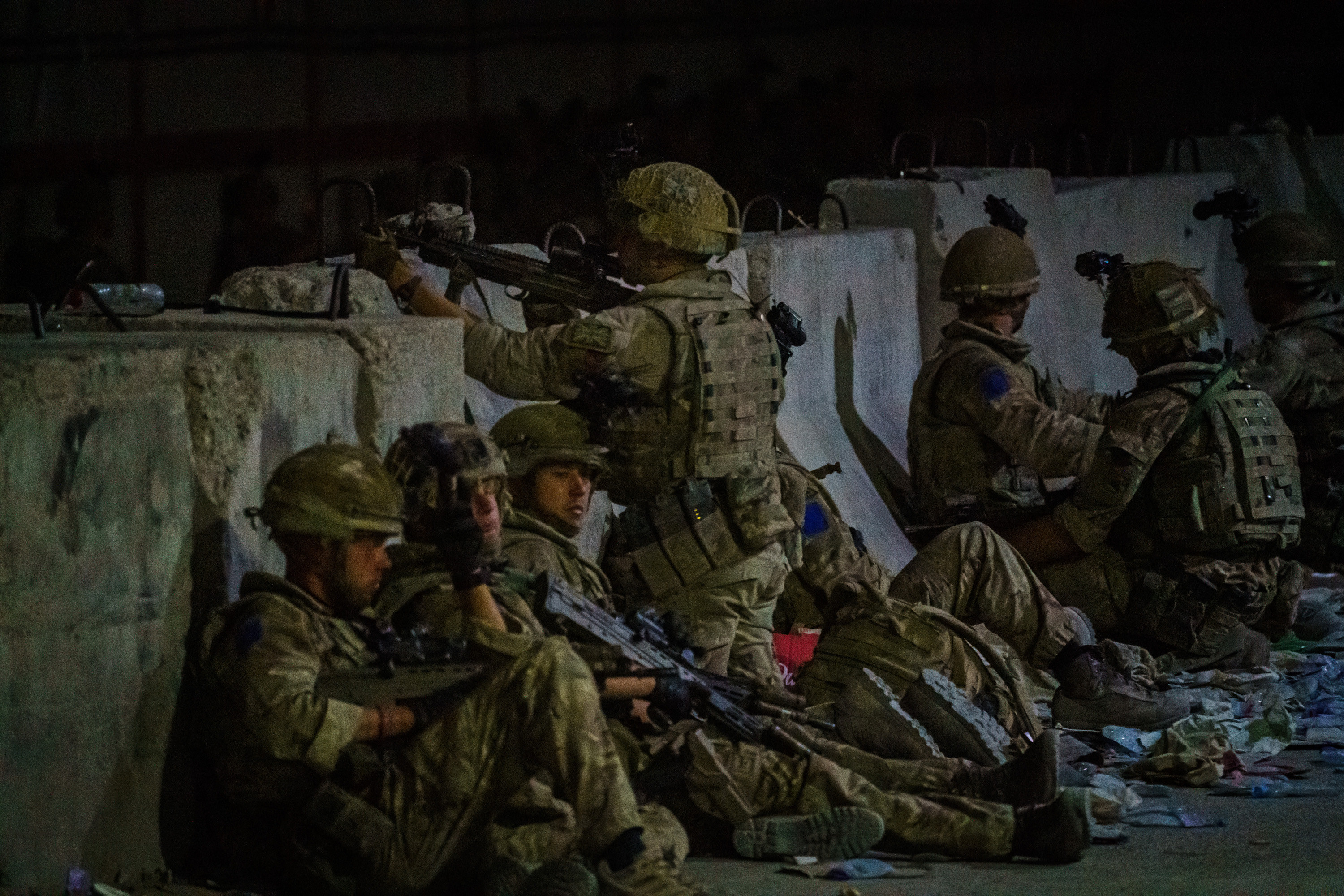 Military soldiers sit behind a wall, one looking over the barrier through their gun scope