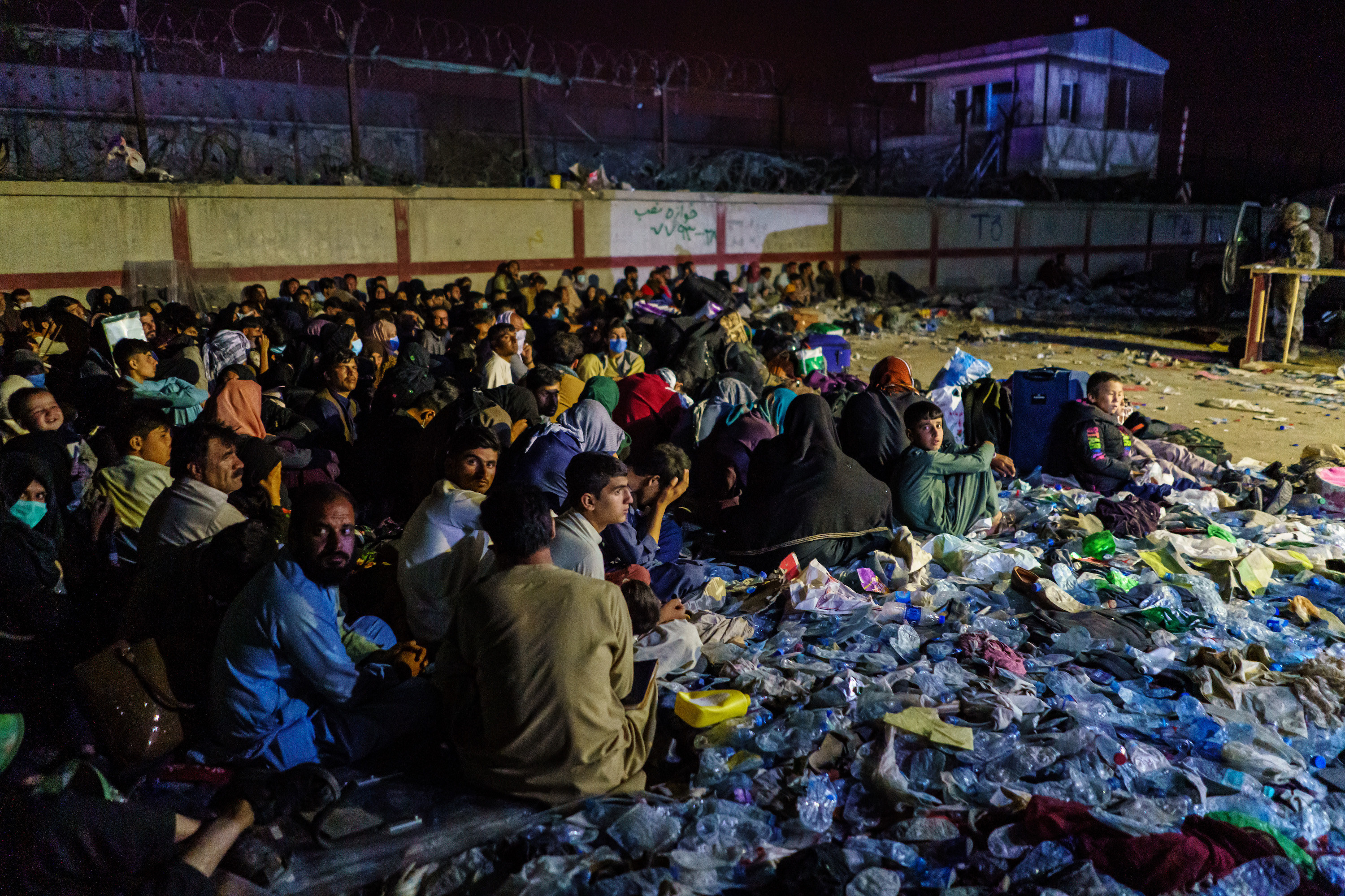 A crowd sits in the dark near armed soldiers