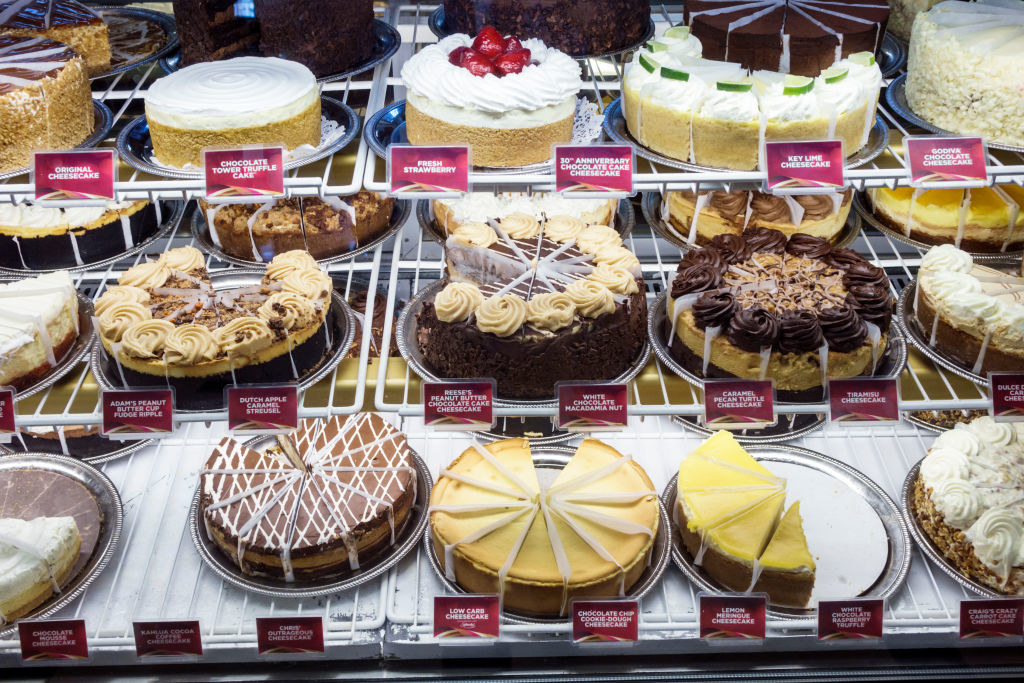 A display of many cakes and other desserts, including cheesecake