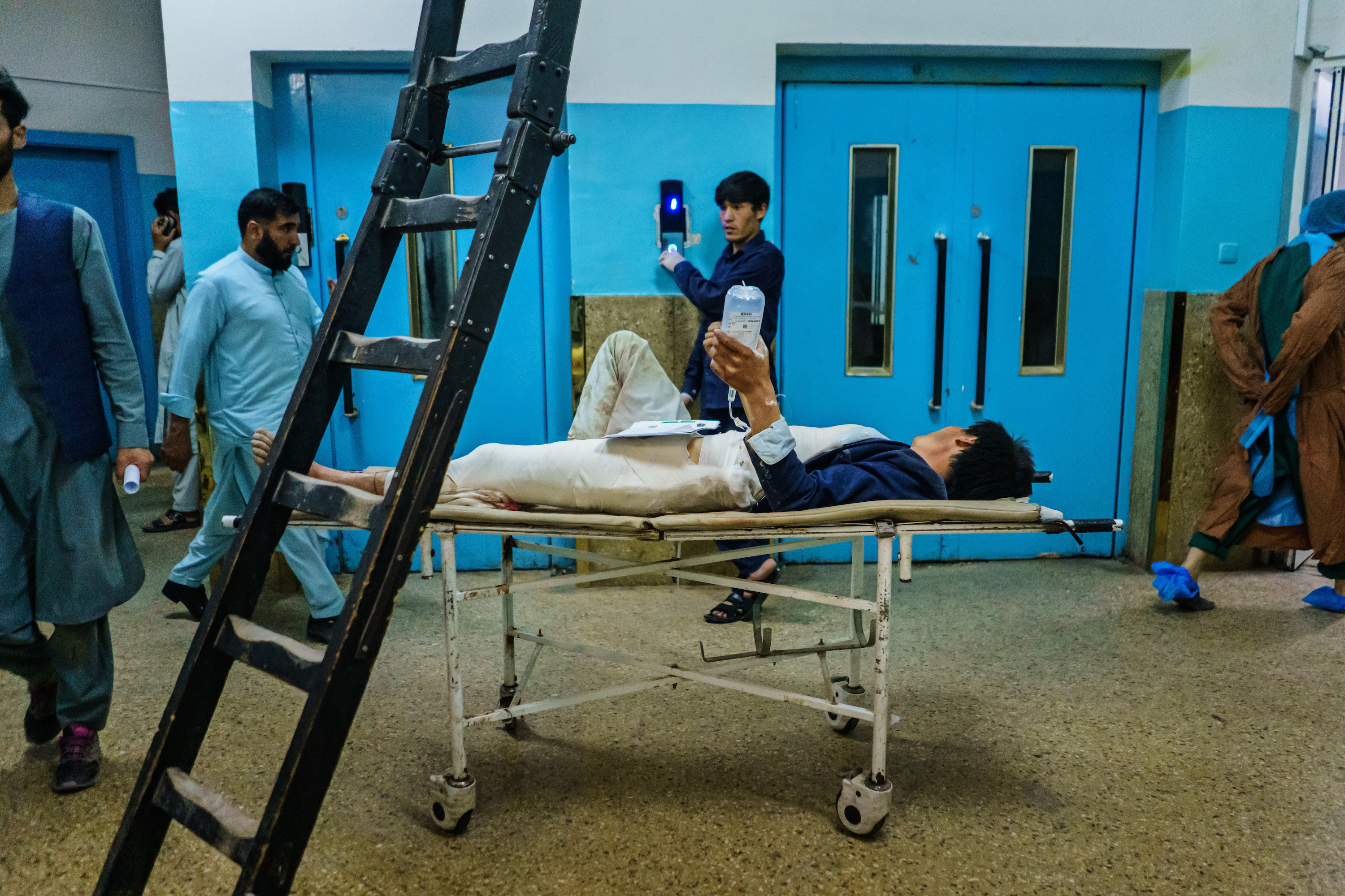 An injured person lying on a hospital bed holds an IV drip