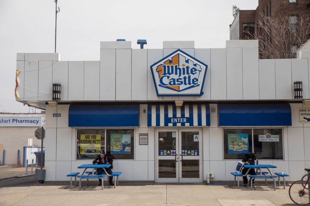 The outside of a White Castle restaurant with two people sitting at the tables in front