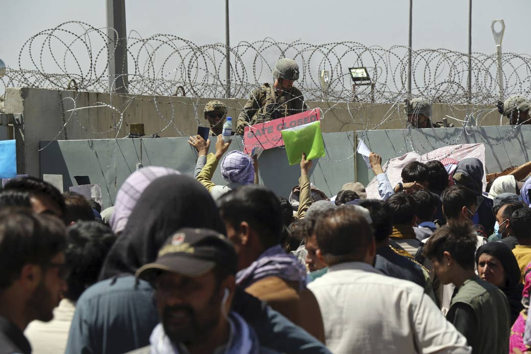 """A large crowd gathers outside a gate at the airport in Kabul as a guard posts a sign that reads """"Gate Closed"""""""