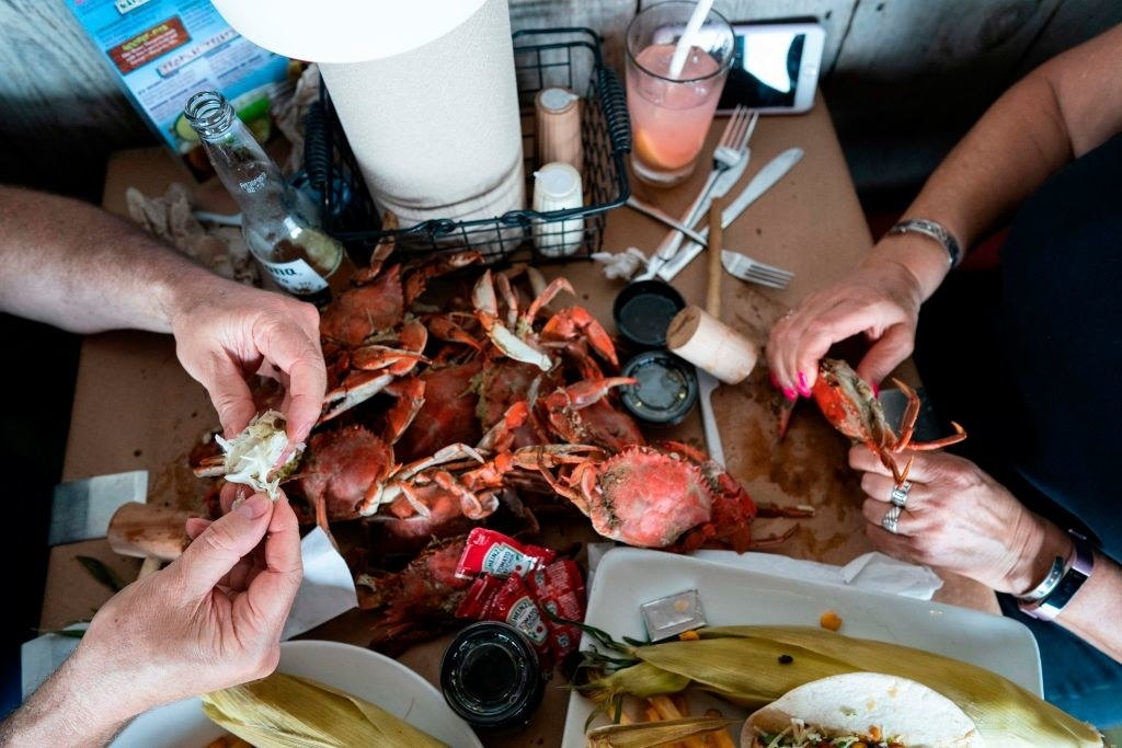 Two people sitting at a table and eating crab