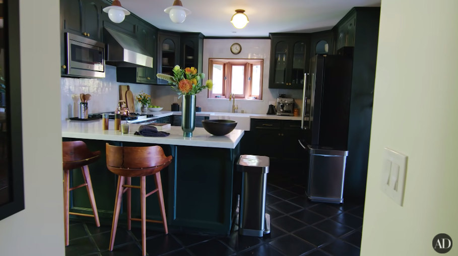 A kitchen with dark-toned cupboards and dark floor tiles