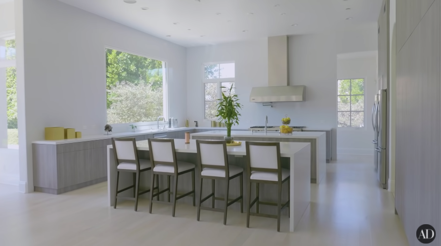 A large, very spare white kitchen with an island and large windows