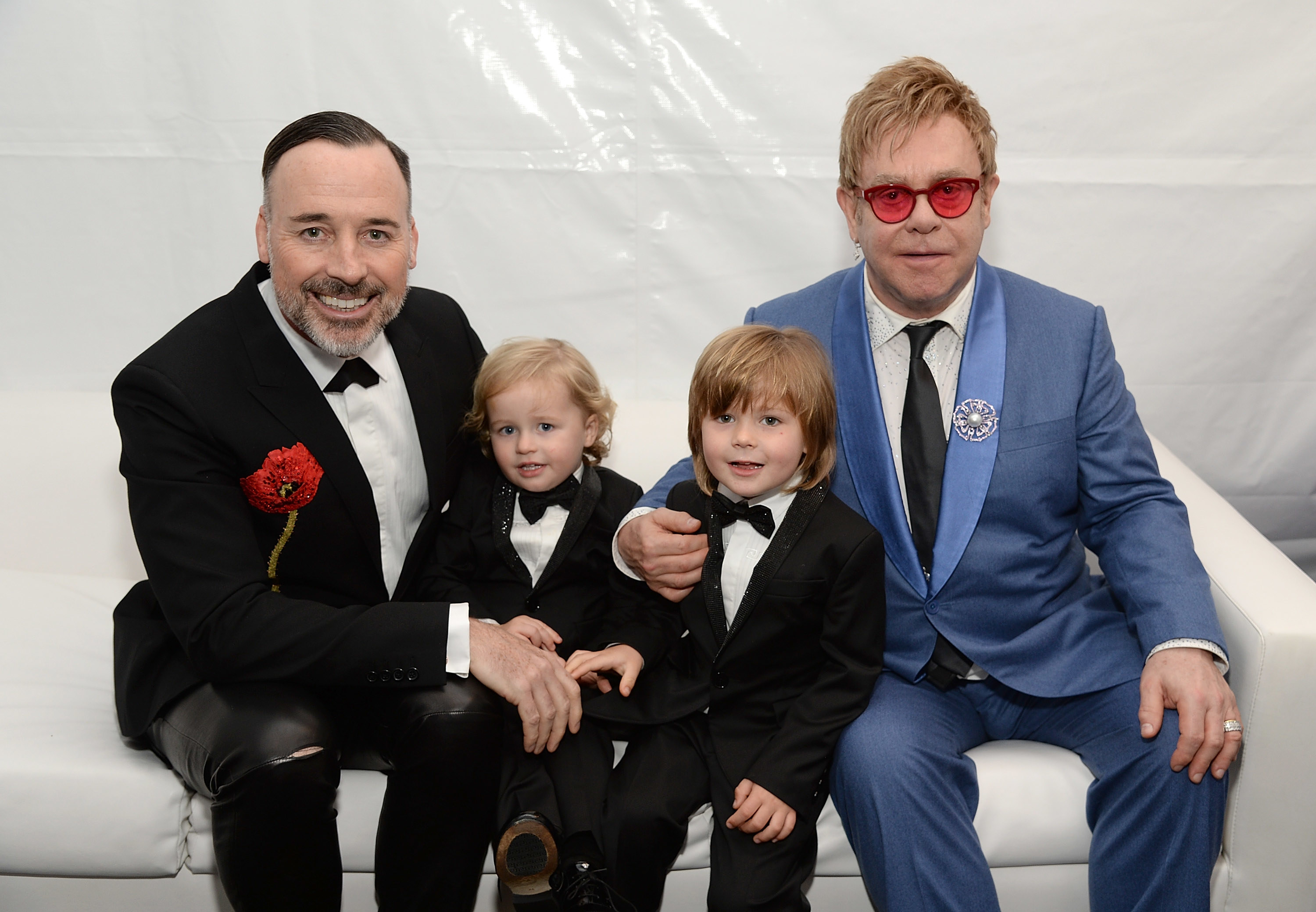 David and Elton sit on a couch and put their arms around their young twin sons