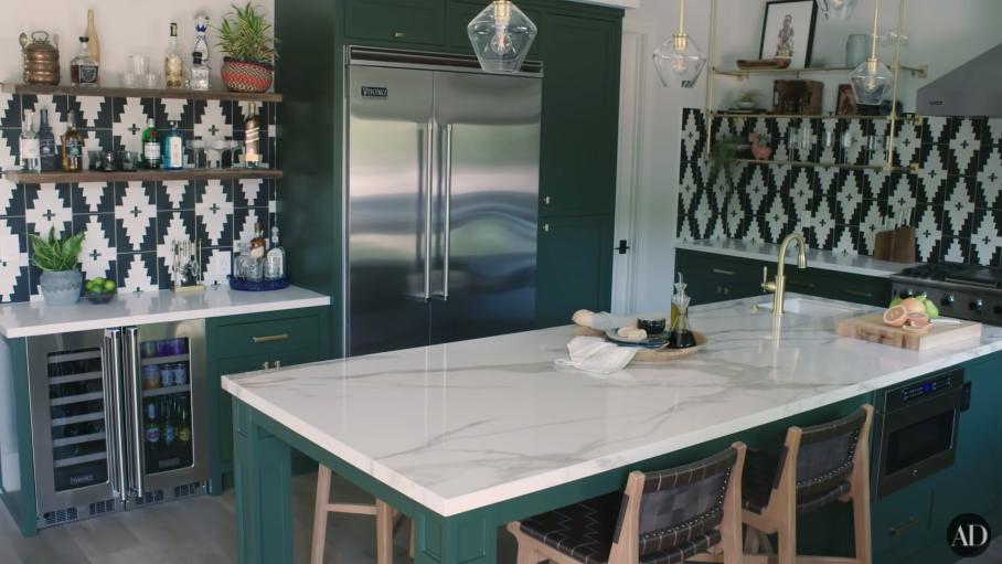 A dark-green kitchen with an island