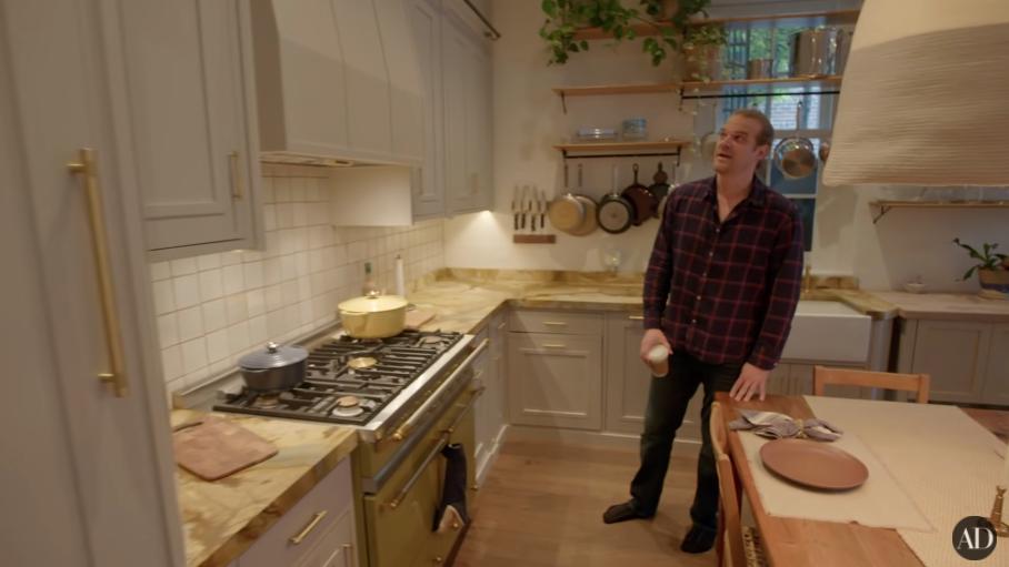 David Harbour standing in his kitchen