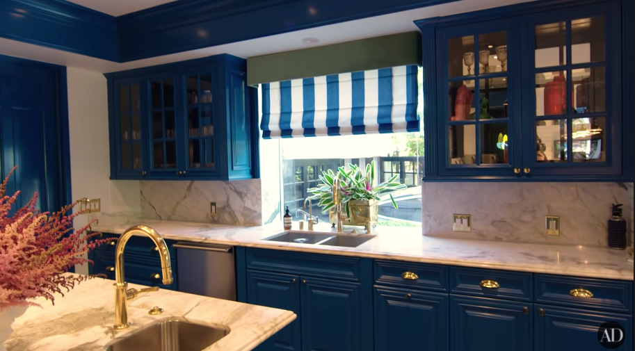 A kitchen with blue cupboards and marble tops