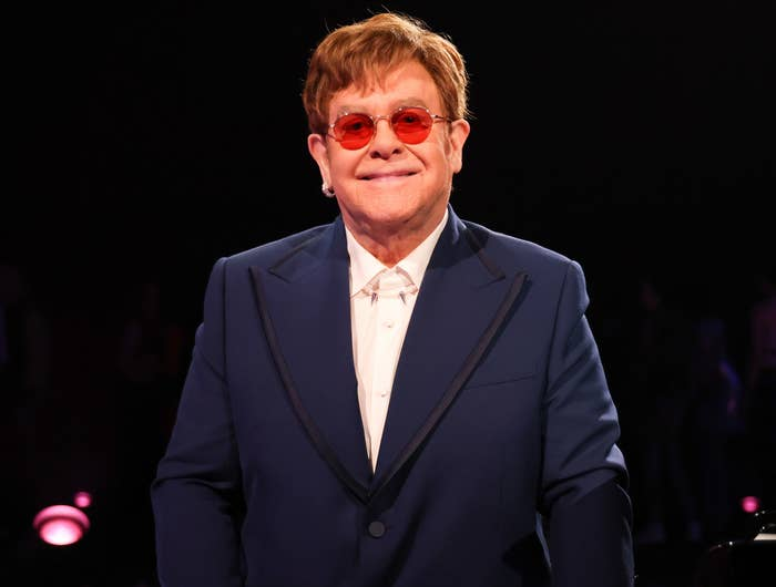 Elton wears a navy tux and red tinted glasses