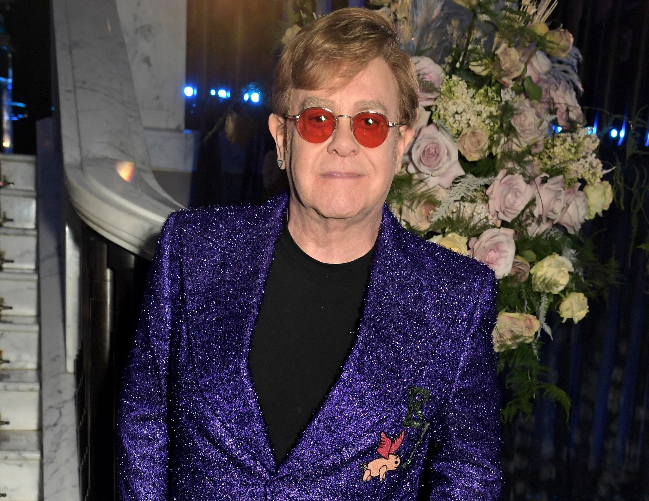 Elton wears a purple sparkly blazer and red tinted glasses