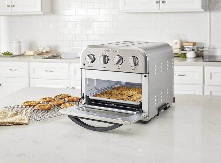 chocolate chip cookies being baked in the little oven on a counter