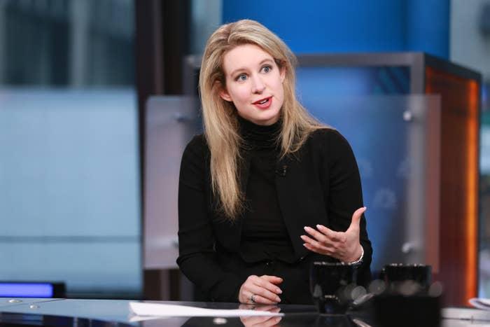 Elizabeth in her trademark black turtleneck sits at a desk