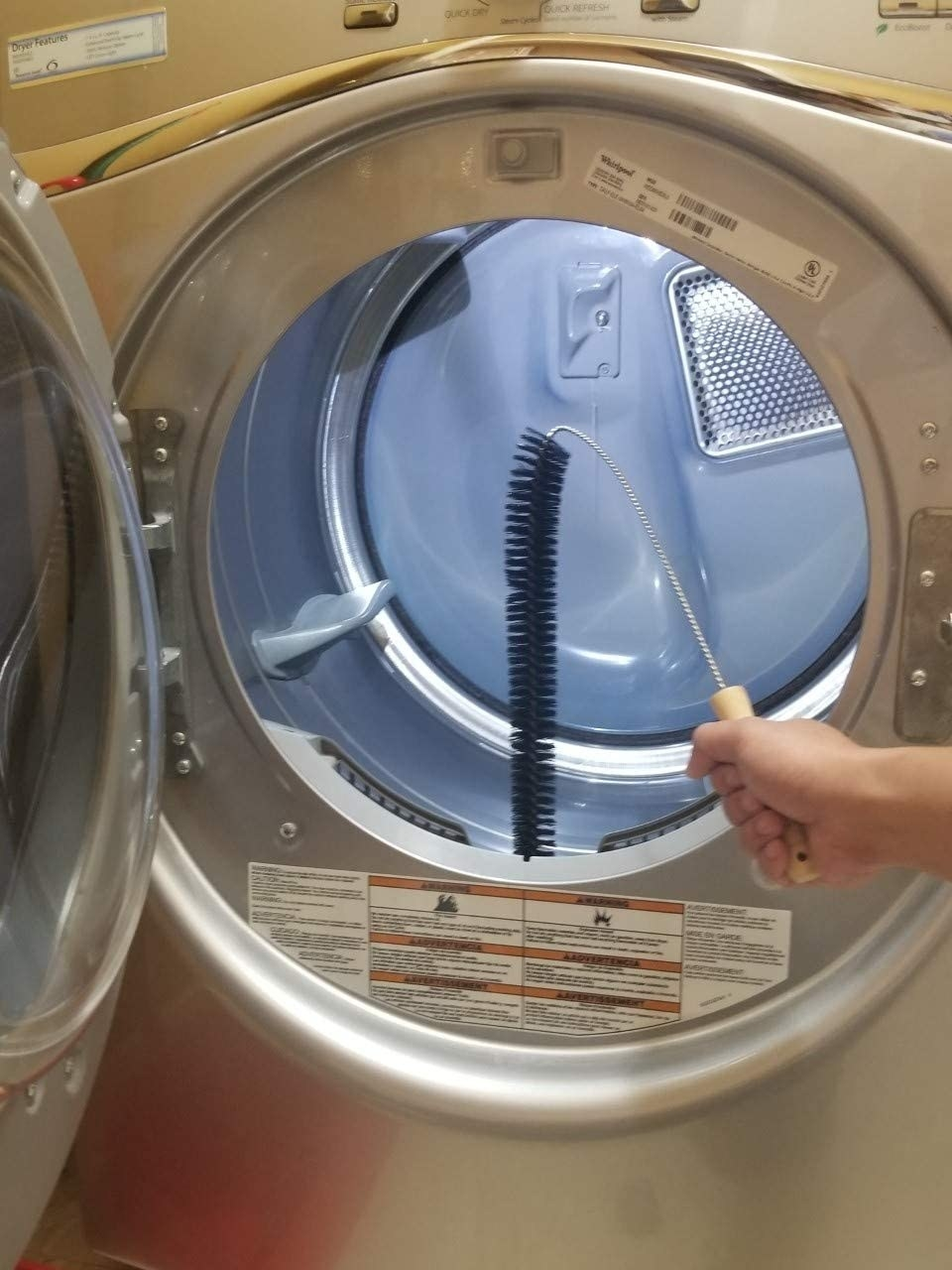 person using long brush to clean out the lint trap in a front-load clothes dryer