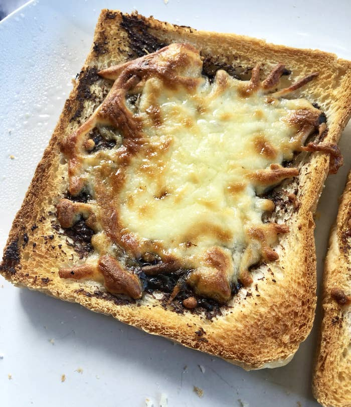 A closeup of a piece of toast that has Vegemite and melted cheese