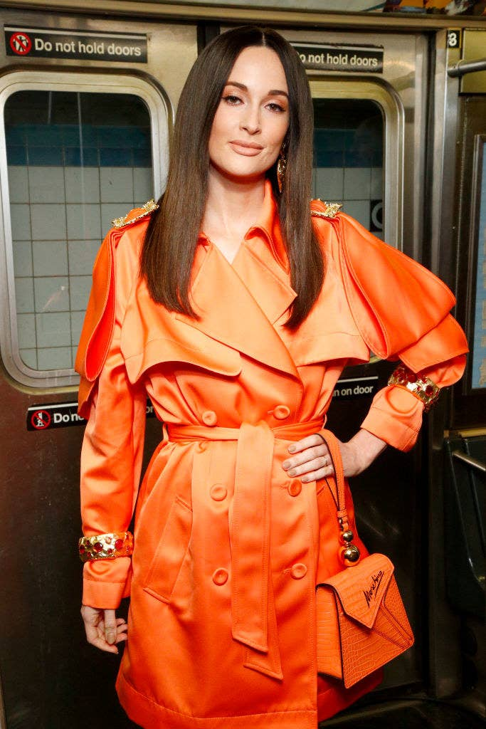 Kacey Musgraves attends the Moschino Prefall 2020 Runway Show in a brightly-colored trench coat with matching purse