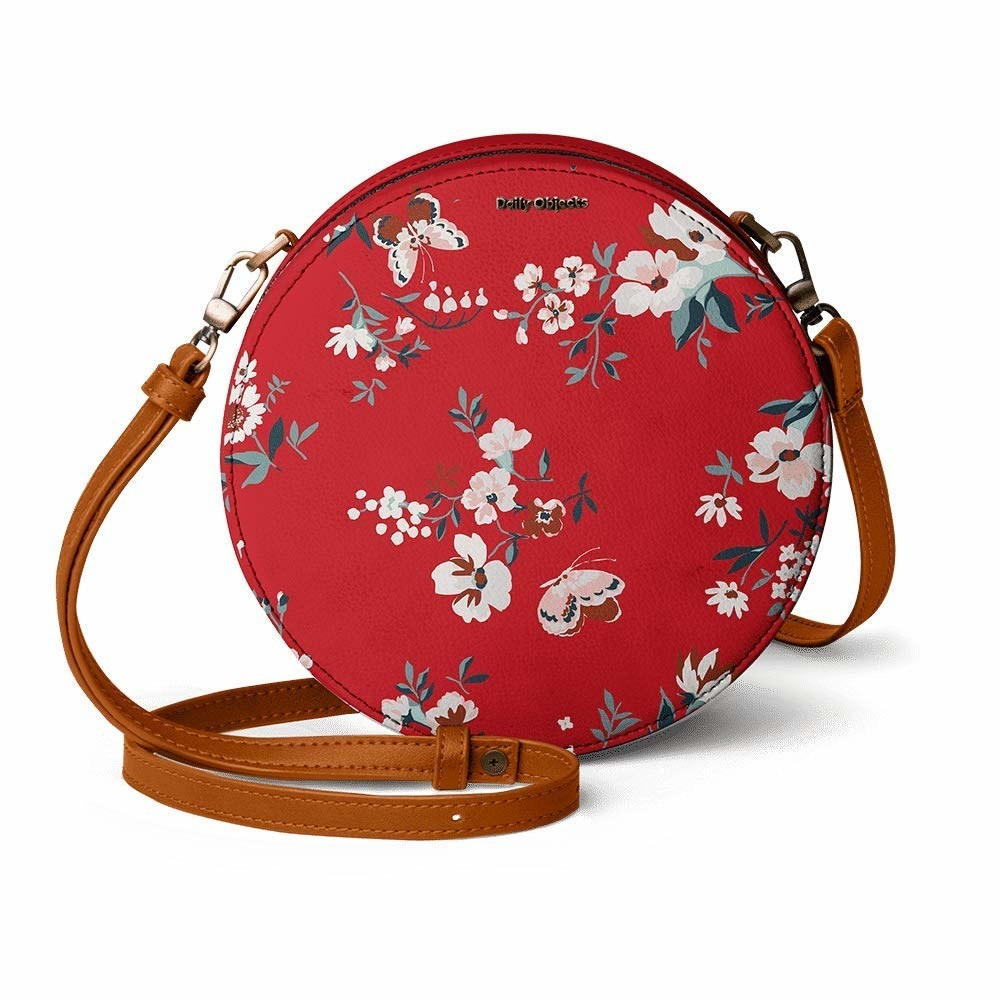 A round red sling bag with a floral print and tan straps