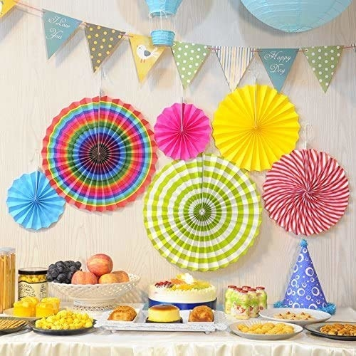 6 fans in different colours and sizes hung on a wall behind a table laden with food