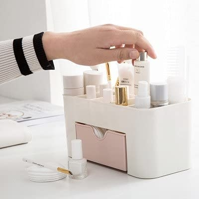 A hand pulling out a small bottle of product from the organiser
