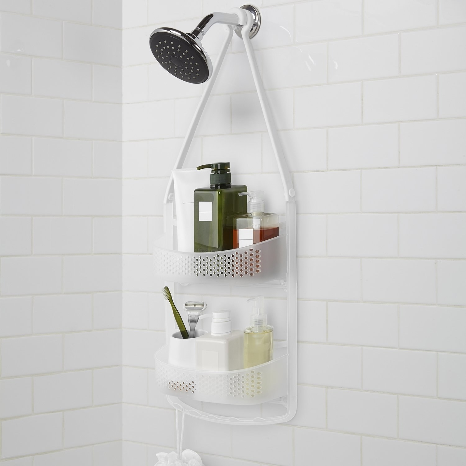 A shower caddy with shampoo, shower gel, a razor and miscellaneous bath essentials hung over a shower head on a white tiled bathroom wall