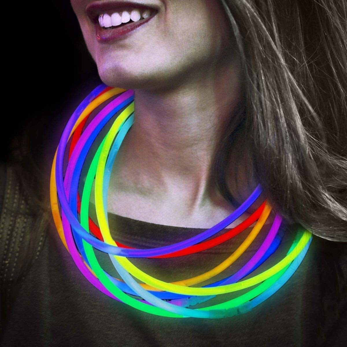 A person wearing lit up glow sticks as necklaces around her neck