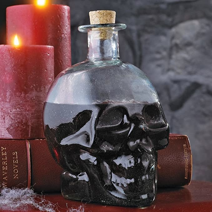 A skull shaped decanter with a drink in it