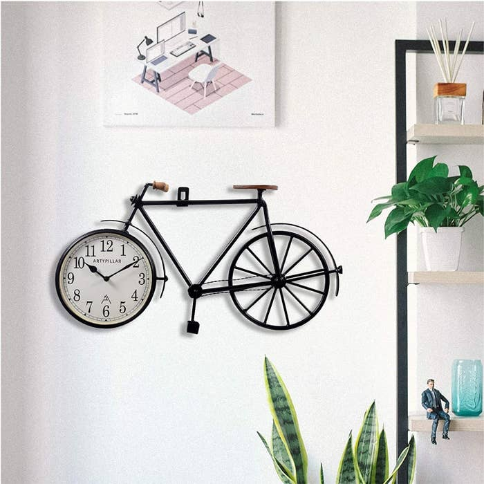 A wooden bicycle with a wall clock adorning its front wheel