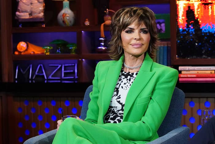 Lisa in a brightly colored pantsuit sitting for a late night interview