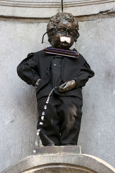 statue of a little boy peeing, and he's dressed up like a famous harmonica player