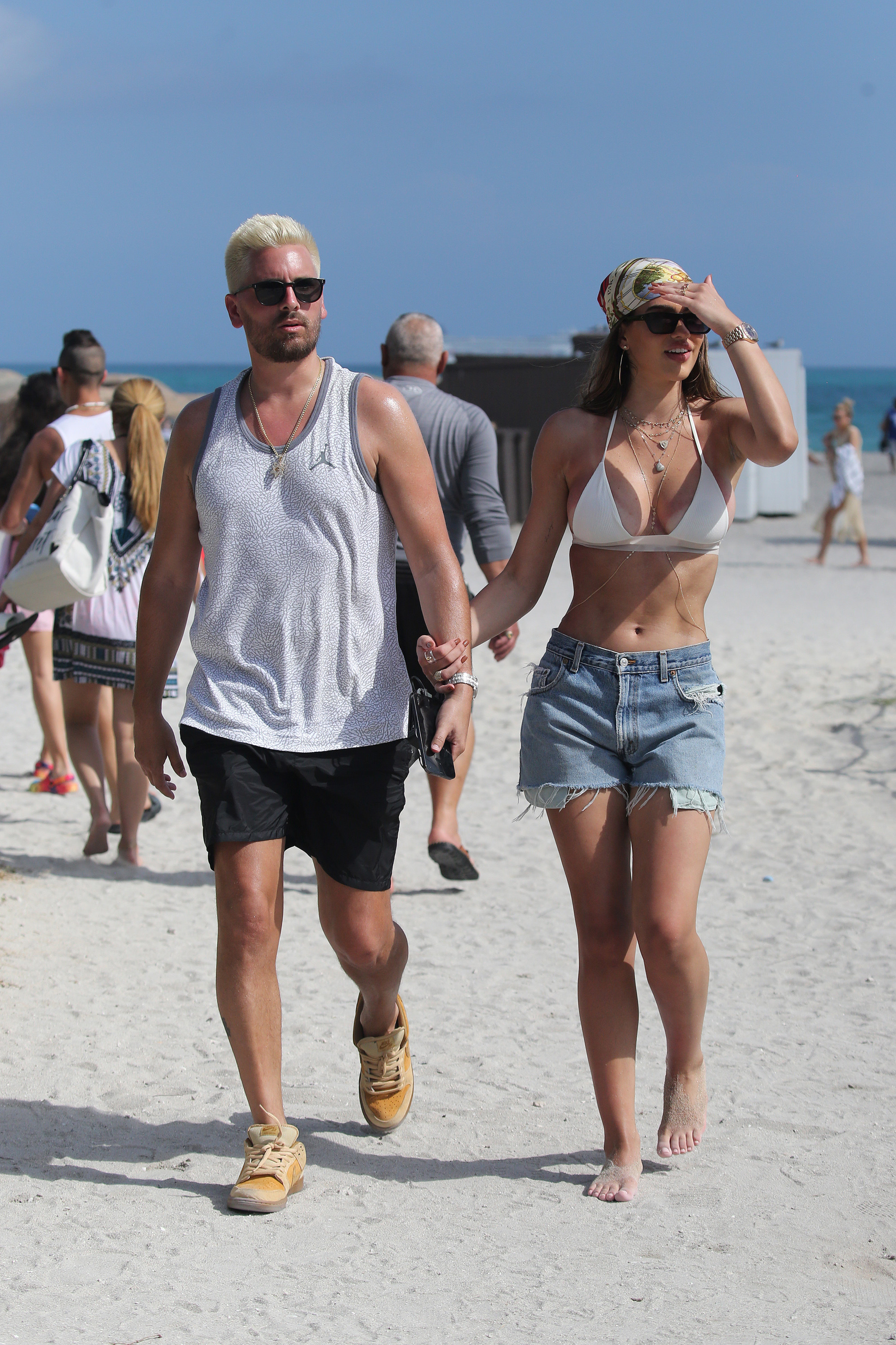 Scott and Amelia walking hand in hand on the beach