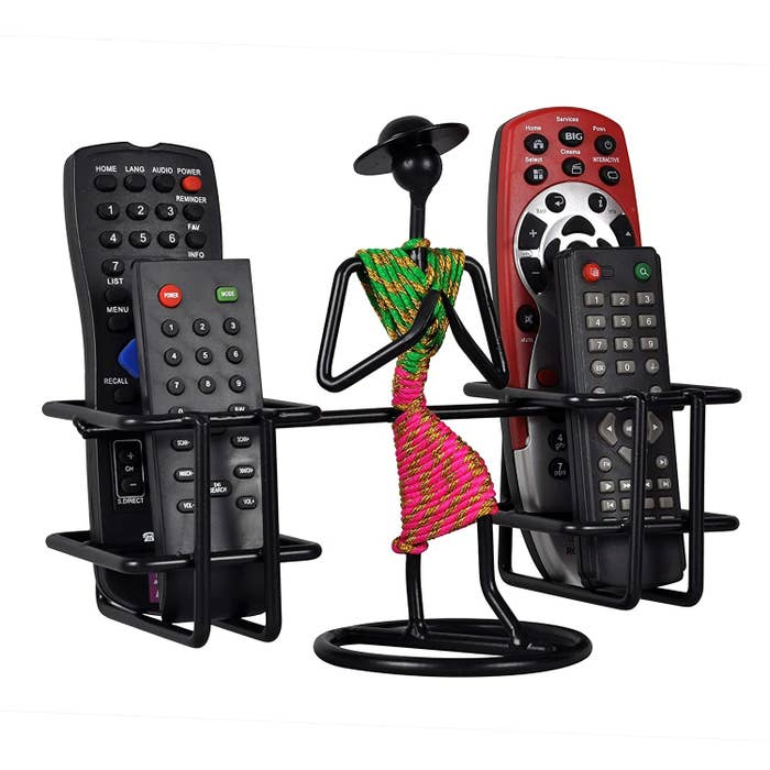 A metal remote holder with a metal lady in the middle in green and pink folding her hands
