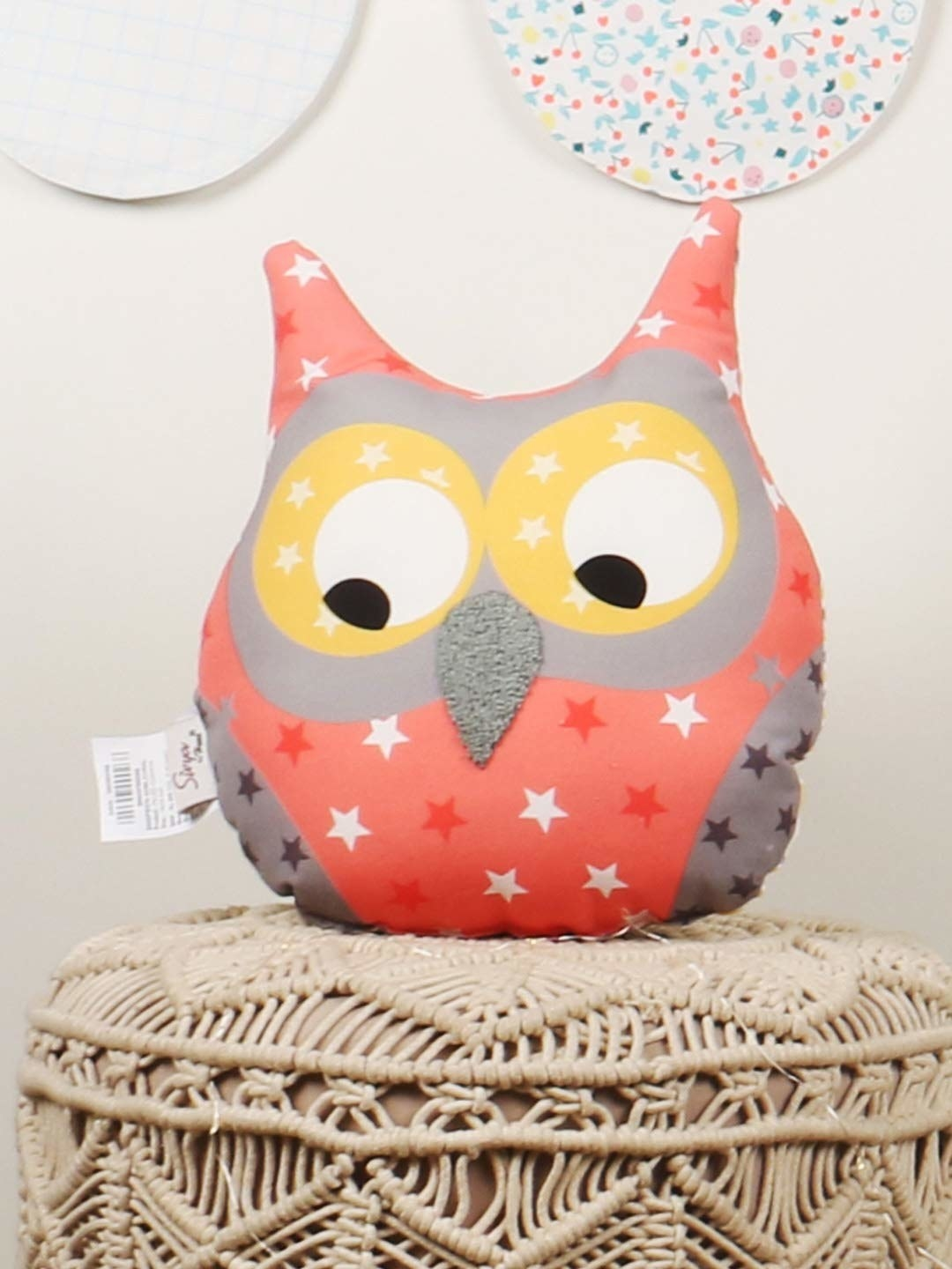 A colourful owl cushion that has its eyes averted away